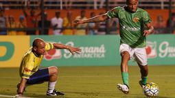 Gelandang Brasil, Gabriel Jesus, berusaha melewati Leo pada laga amal. Pertandingan amal yang diikuti sejumlah atlet Brasil ini dilakukan untuk mengenang para pemain Chapecoense yang menjadi korban kecelakaan pesawat. (Reuters/Leonardo Benassatto)