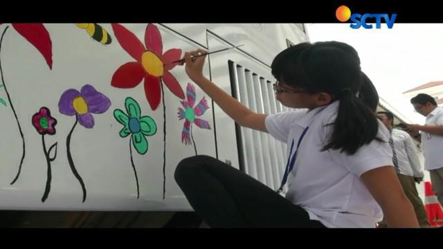 Berbekal cat minyak, ke-10 anak dengan kebutuhan khusus menyapukan kuas lukisnya di atas media yang tidak biasa yakni di badan bus Transjakarta.