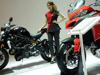 Model berpose disisi motor Ducati Monster 1200R yang dipamerkan di IIMS 2016 di JIEXPO Kemayoran, Jakarta, Selasa (12/4/2016). Dengan tampilan sprty dan ekstrem, Ducati Monster 1200R dibanderol hampir 1,1 miliar rupiah. (Liputan6.com/Helmi Fithriansyah)