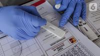 Tenaga medis melihat hasil rapid test massal yang digelar Badan Intelijen Negara (BIN) di lapangan Kecamatan Pamulang, Tangsel, Kamis (2/7/2020). Dengan adanya rapid test yang digelar BIN, Pemkot Tangsel dapat melakukan tracking dan tracing lebih cepat. (Liputan6.com/Fery Pradolo)