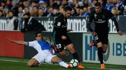 Pemain Real Madrid, Isco berebut bola dengan pemain Leganes, Gabriel Appelt pada partai tunda pekan ke-16 La Liga Spanyol di Estadio Municipal de Butarque, Rabu (21/2). Real Madrid menang 3-1 atas Leganes meski sempat ketinggalan. (AP/Francisco Seco)
