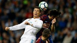 Pemain Real Madrid, Cristiano Ronaldo berebut bola dengan pemain Eibar, Paulo Oliveira dalam lanjutan La Liga pekan kesembilan di Stadion Santiago Bernabeu, Minggu (22/10). Madrid menang tiga gol tanpa balas. (AP/Francisco Seco)