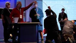 Tim produksi memeriksa kaca plexiglass di atas panggung yang akan berfungsi sebagai penghalang untuk mengurangi resiko penyebaran COVID-19 saat persiapan untuk debat calon wakil presiden AS di Universitas Utah, Salt Lake City, Selasa (6/10/2020). (AP Photo/Julio Cortez)