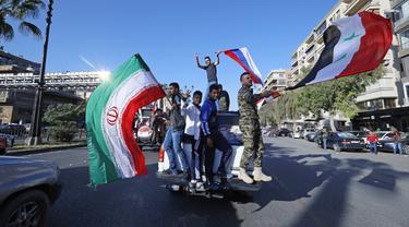 Pendukung pemerintah mengibarkan bendera Suriah, Iran, dan Rusia saat berdemonstrasi di Damaskus, Suriah, 14 April 2018. Suriah tengah mengalami gejolak krisis ekonomi dengan nilai tukar mata uang yang merosot dalam beberapa hari terakhir. (AP Photo/Hassan Ammar, File)