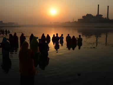 Umat Hindu India mengambil bagian dalam ritual pemujaan dewa matahari selama Festival Chhath Puja di tepi sungai Sabarmati, Ahmedabad, Selasa (13/11). Festival Hindu kuno ini dilakukan sebagai bentuk terima kasih kepada Dewa Matahari (SAM PANTHAKY/AF/AFP)
