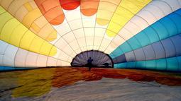Salah satu tim mempersiapkan balon udara pada festival internasional Sagrantino di kawasan Umbria, Italia, 22 Juli 2018. Puluhan balon udara berkompetisi menghadapi tantangan dalam festival yang memperebutkan piala perak tersebut. (AFP PHOTO/TIZIANA FABI)