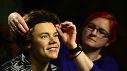 Seorang pegawai tampak merapikan patung salah satu member One Direction, Harry Styles, di museum lilin Madame Tussauds, London, Rabu (6/8/14). (AFP PHOTO/Carl COURT)
