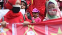 Seorang anak terlihat dalam aksi unjuk rasa menolak pengesahan UU Omnibus Law Cipta Kerja di Kawasan Patung Kuda, Jakarta, Jumat (16/10/2020). Meski sudah ada imbauan untuk tidak membawa anak-anak dalam aksi unjuk rasa namun sejumlah orang tua tetap menyertakan. (Liputan6.com/Helmi Fithriansyah)