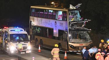 Petugas pemadam kebakaran, petugas medis, dan polisi berkumpul dekat bus tingkat dua yang menabrak pohon di Kwu Tung, Hong Kong, Rabu (18/12/2019). Kecelakaan tersebut mengakibatkan enam orang tewas dan belasan lainnya luka-luka. (Philip FONG/AFP)