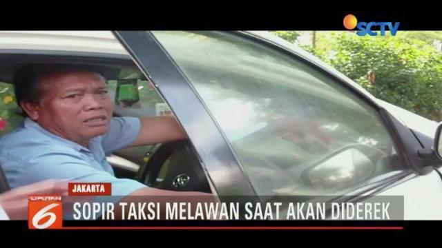 Tidak merasa parkir sembarangan, sopir taksi ini menolak dan melawan saat akan diamankan Sudin Perhubungan Jakarta Barat yang tengah menggelar razia parkir liar.