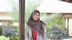Anisa tidak jarang juga tampil dengan busana yang sedikit formal. Blazer berwarna abu-abu serta hijab berwarna gelap dipadukan dengan busana orange membuat penampilannya tetap menawan. (Liputan6.com/IG/@anisarahma_12)