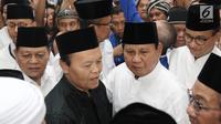 Bakal Calon Presiden, Prabowo Subianto didampingi Wakil Ketua Majlis Syuro PKS Hidayat Nur Wahid berjalan keluar dari Masjid Sunda Kelapa menuju Gedung KPU RI untuk mendaftarkan diri sebagai capres, di Jakarta, Jumat (10/8). (Liputan6.com/Herman Zakharia)