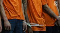Tersangka kasus kerusuhan Aksi 22 Mei diikat pada bagian tangan saat dihadirkan dalam rilis di Polda Metro Jaya, Jakarta (22/5/2019). Polda Metro Jaya mengamankan 257 orang dari tiga lokasi pada dini hari tadi. (Liputan6.com/JohanTallo)