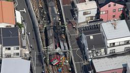 Pandangan dari udara menunjukkan kereta tergelincir setelah menabrak truk di Yokohama, Prefektur Kanagawa, Jepang, Kamis (5/9/2019). Kecelakaan yang terjadi di jalur rel menuju Tokyo ini membuat truk itu terbakar. (Kenzaburo Fukuhara/Kyodo News via AP)