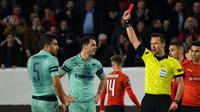 Wasit Ivan Kruzliac mengeluarkan kartu merah untuk Sokratis pada leg 1, babak 16 besar Liga Europa yang berlangsung di Stadion Roazhon Park, Rennes, Jumat (8/3). Arsenal kalah 1-3 kontra Rennes. (AFP/Damien Meyer)