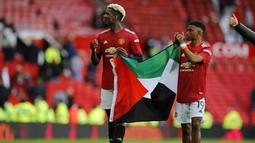 Tak lama berselang, Amad Diallo mengikuti Pogba untuk bersama-sama membentangkan bendera tersebut dan menunjukkannya ke arah penonton di tribun Old Trafford. (Foto: AFP/Pool/Phil Noble)