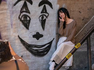 Seorang wanita berpose dekat lukisan wajah Joker di tangga di kawasan Bronx, New York, 23 Oktober 2019. Tangga yang terletak tepat di West 167th Street itu menjadi buruan wisatawan, terutama para penggemar film Joker yang ingin berfoto. (Don Emmert / AFP)