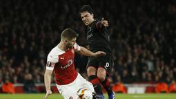 Aaron Ramsey mencoba menghentikan Gerzino Nyamsi pada leg kedua,babak 16 besar Liga Europa yang berlangsung di Stadion Emirates, London, Jumat (15/3). Arsenal menang 3-0 atas Rennes. (AFP/Ian Kington)
