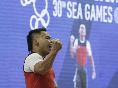 Lifter Eko Yuli usai melakukan angkatan saat SEA Games 2019 cabang angkat besi nomor 61 kg di Stadion Rizal Memorial, Manila, Minggu (1/12). Dirinya meraih emas dengan total angkatan 309 kg. (Bola.com/M Iqbal Ichsan)