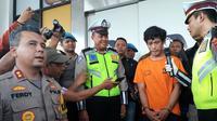 Pelanggar lalu lintas, Adi Saputra (21) yang merusak kendaraannya saat ditilang polisi, menangis di Polres Tangerang Selatan. (Liputan6.com/Pramita Tristiawati)