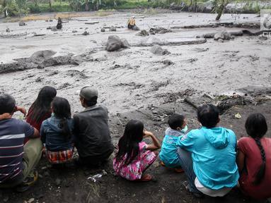 Warga mengamati aliran lahar dingin yang melintasi Sungai Yeh Sah di Karangasem, Bali, Sabtu (2/12). Banjir lahar dingin dari Gunung Agung tersebut mengundang perhatian warga sekitar. (Liputan6.com/Immanuel Antonius)