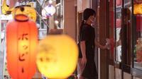 Seorang pekerja mengenakan masker mencegah penyebaran coronavirus baru membersihkan jendela sebuah pub Jepang di Tokyo, Senin, (20/7/2020). Ibukota Jepang hari Senin mengkonfirmasi lebih dari 160 kasus virus corona baru. (AP Photo/Eugene Hoshiko)