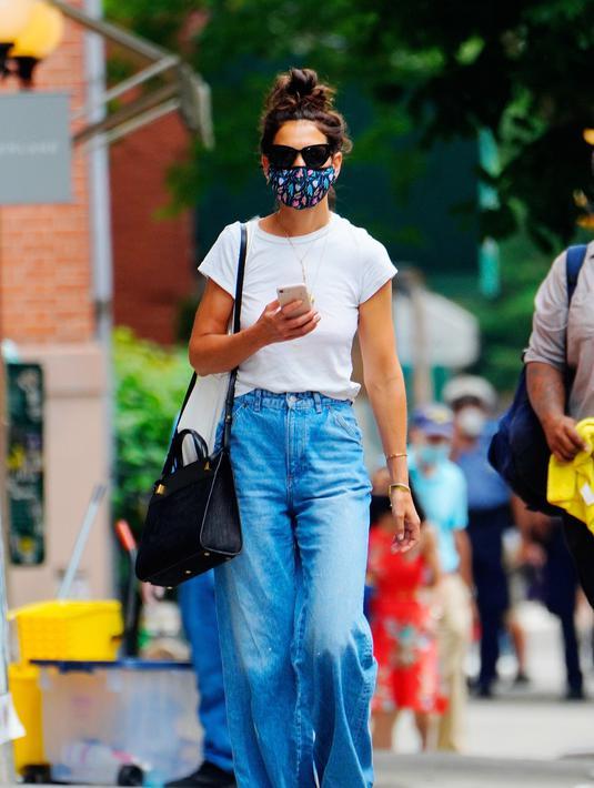 Katie Holmes tampil kasual untuk musim panas dengan celana jeans wide legs, sepatu kets, dan tas Métier London Perriand. Foto: Vogue.