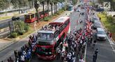 Bus tingkat dengan kap terbuka membawa pelari Torch Relay Asian Games 2018 di Jalan Jendral Sudirman, Jakarta, Sabtu (18/8). Hari terakhir kirab obor Asian Games ini api abadi dibawa dari Tugu Monas hingga Gelora Bung Karno. (Liputan6.com/ Fery Pradolo)
