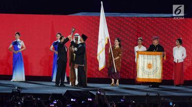 Gubernur DKI Jakarta Anies Baswedan menyerahkan obor Asian Games kepada Wali Kota Hangzhou China saat penutupan Asian Games 2018 di Stadion Utama GBK, Jakarta, Minggu (2/9). (Merdeka.com/Imam Buhori)