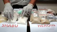 Salah satu petugas merapikan barang bukti narkotika jenis sabu saat jumpa pers di Dit Resnarkoba Polda Metro Jaya, Kamis (13/11/2014). Sebanyak 19,3 kg shabu dan 1,03 heroin disita Dit Resnarkoba Polda Metro Jaya. (Liputan6.com/Helmi Fithriansyah)
