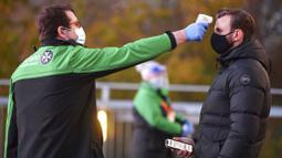 Petugas memeriksa suhu tubuh suporter West Ham United sebelum menyaksikan pertandingan melawan Manchester United di Stadion London, Sabtu (5/12/2020). (Justin Setterfield/Pool Via AP)