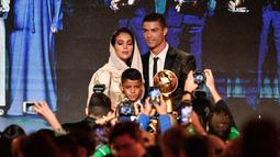 Georgina Rodriguez foto bersama dengan kekasihnya Cristiano Ronaldo dan putranya Cristiano Jr diatas panggung selama Dubai Globe Soccer Awards ke-10 di Dubai (3/1). (AFP Photo/Fabio Ferrari)