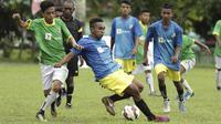 Pemain SSB Hatu berebut bola dengan pemain SSB Maehanu pada semifinal turnamen Liga Remaja UC News di Lapangan Masariku Yonif 733, Ambon, Rabu (29/11/2017). (Bola.com/Peksi Cahyo)