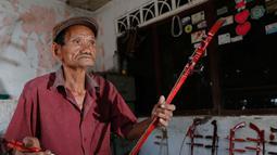 Ghohyong memainkan alat musik Tehyan khas Tionghoa buatannya di Neglasari, Kota Tangerang (5/2/2021). Akibat pandemi Covid-19 membuat pria tua tersebut tidak menerima orderan pembuatan alat musik Tehyan.  (Liputan6.com/Angga Yuniar)