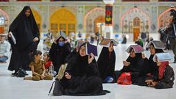Para jemaah syiah manaruh kitab suci Al-Quran di atas kepala mereka saat menyambut malam lailatul qadar di Makam Suci Imam Ali, Najaf, Irak, Sabtu (16/5/2020). Ritual saat berdoa dan meminta hajat kepada Tuhan ini sudah berlangsung selama berabad-abad lamanya. (HAIDAR HAMDANI/AFP)