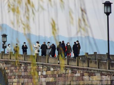 Orang-orang mengunjungi kawasan Danau Barat yang indah di Hangzhou, Provinsi Zhejiang, China timur (19/2/2020). Taman-taman dan objek wisata yang tergabung dalam kawasan Danau Barat telah dibuka kembali secara teratur pada Rabu (19/2). (Xinhua/Zheng Mengyu)