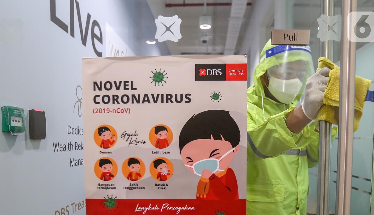 Petugas membersihkan gagang pintu di kantor DBS Tower, Jakarta, Selasa (30/6/2020). Bank DBS Indonesia menerapkan protokol kesehatan dengan penyemprotan cairan desinfektan dan melakukan pelapisan antimicrobial di area kantor untuk mencegah penyebaran virus Covid-19. (Liputan6.com/Fery Pradolo)