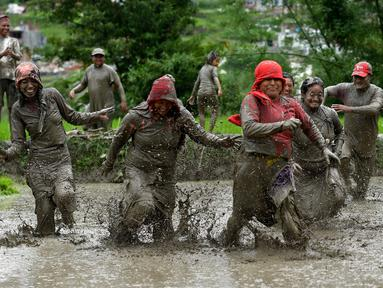 Para petani berlumur lumpur saat bermain pada Hari Padi Nasional di sawah Desa Tokha, Kathmandu, Nepal, Senin (29/6/2020). Para petani di Nepal merayakan Hari Padi Nasional sebagai musim tanam padi tahunan dimulai. (PRAKASH MATHEMA/AFP)