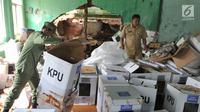 Petugas kecamatan menyelamatkan kotak suara kardus yang sebagian rusak terendam banjir di gudang tempat penyimpanan logistik di Kecamatan Ciseeng, Bogor, Senin (15/4). Lebih dari 600 kotak suara rusak akibat tembok gudang jebol diterpa hujan lebat dan angin kencang semalam. (merdeka.com/Arie Basuki)