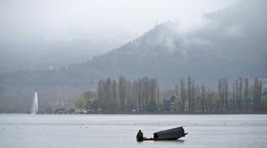 Seorang awak perahu Kashmir mengayuh sebuah perahu saat hujan di Danau Dal di Srinagar (20/3). Danau Dal dijuluki sebagai Jewel in the Crown of Kashmir atau Srinagar Jewel. (AFP Photo/Tauseef Mustafa)