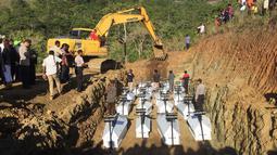 Pemakaman massal korban banjir bandang di Sentani, Kabupaten Jayapura, Papua, Rabu (27/3). Prosesi pemakaman dihadiri oleh sejumlah pejabat dan tokoh masyarakat di Provinsi Papua.  (NETHY DHARMA SOMBA/AFP)