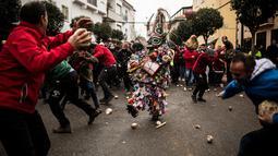 Orang-orang melempari seorang pria berkostum ala setan dengan sayuran lobak selama Festival Jarramplas di kota Piornal, Spanyol, Sabtu (19/1). Sembari dilempari lobak, sang Jarramplas tetap berjalan dan terus memukul drum yang dibawanya. (AP/Javier Fergo)