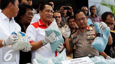 Kepala BNN, Komjen Budi Waseso (tengah) menunjukan barang bukti ekstasy saat rilis di Mapolda Metro Jaya, Jakarta, Rabu (7/10/2015).  47kg shabu dan 520 ribu butir ekstasy berhasil diamankan dari 4 orang tersangka. (Liputan6.com/Yoppy Renato)