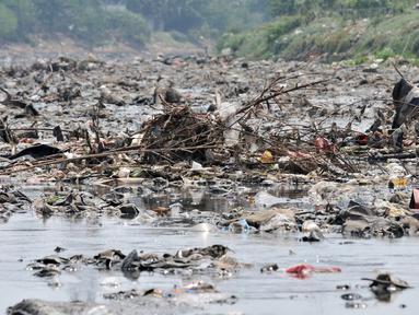 Tumpukkan sampah yang muncul di permukaan Kanal Banjir Barat, Jakarta, Selasa (16/7/2019). Kemarau sejak dua bulan terakhir ini menyebabkan sampah-sampah yang mengendap di dasar sungai muncul ke permukaan sehingga menimbulkan bau tak sedap. (merdeka.com/Iqbal S Nugroho)