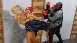 Seorang wanita mengenakan sarung tinju berpose di depan gambar 3 dimensi Presiden AS Donald Trump di Museum of Illusions, Hollywood, California (27/3). Di pameran ini pengunjung bisa berfoto dengan gaya yang unik dan terihat nyata.(AFP Photo/Mark Ralston)