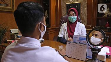 drg. Ayusha berbincang dengan pasien di salah satu klinik di kawasan Pulo Gadung, Jakarta, Rabu (22/4/2020). Di tengah pandemi COVID-19 seperti sekarang ini, drg. Ayusha akan mengenakan alat perlindungan diri (APD) saat memeriksa pasien. (Liputan6.com/Herman Zakharia)