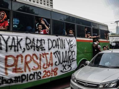 Suporter Persija berada di dalam bus melewati jalan Gatot Subroto menuju stadion Gelora Bung Karno, Jakarta, Minggu (9/12). Antusiasme ribuan suporter Persija bersiap mendukung tim kesayangannya bertanding melawan Mitra Kukar. (Liputan6.com/Faizal Fanani)