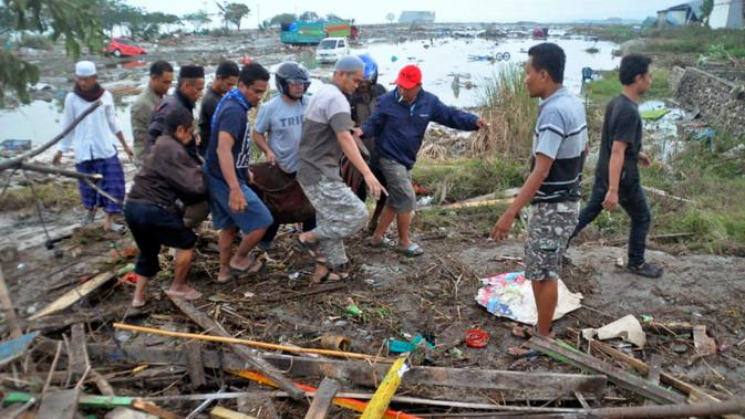 Warga mengevakuasi kantong jenazah berisi jasad korban tsunami di Palu, Sulawesi Tengah , Sabtu (29/9). Gelombang tsunami setinggi 1,5 meter yang menerjang Palu terjadi setelah gempa bumi mengguncang Palu dan Donggala. (AP Photo)#source%3Dgooglier%2Ecom#https%3A%2F%2Fgooglier%2Ecom%2Fpage%2F%2F10000