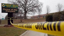 Garis polisi dipasang di sekitar lokasi penembakan di Great Mills High School di Maryland, AS (20/3). Pelaku berusia 17 tahun bernama Austin Wyatt Rollins akhirnya tewas ditembak petugas keamanan. (AP Photo / Alex Brandon)
