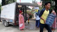 Pengungsi korban gempa dan tsunami Palu membawa galon usai mengisi air dari mobil instalasi pengolahan air Kementerian Pekerjaan Umum dan Perumahan Rakyat (PUPR) di halaman kantor Wali Kota Palu, Sulawesi Tengah, Senin (8/10). (Liputan6.com/Fery Pradolo)
